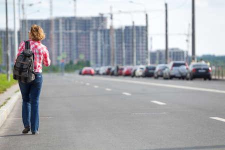 Rear view at Caucasian female hitchhiker walking on asphalt road in urban street, copyspace Stock Photo