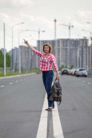 Middle age Caucasian woman waving hand for stop the car, standing on the median strip lines of urban road