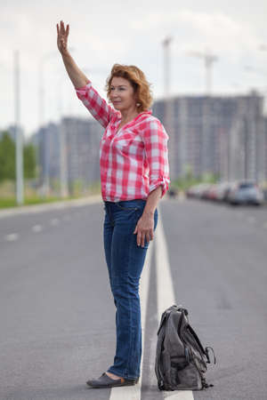 Mature Caucasian woman waving hand for stop the car, standing in the middle of urban road Stock Photo