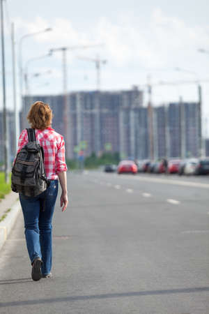 Rear view at woman hitchhiker walking on asphalt road in urban street, copy space