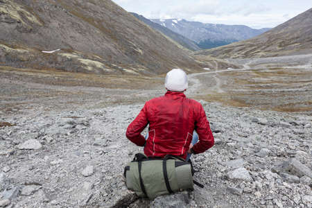 Lonely backpacker sitting on stone and looking at distance, the only one way through the valley, hiking