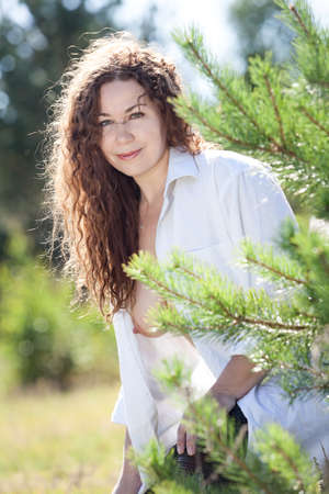 Portrat of pretty Caucasian woman with curly disheveled hair and breast, female standing in sunny forest