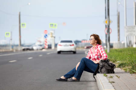 Hitchhiking, passenger car driving away, woman sitting roadside with backpack Stock Photo