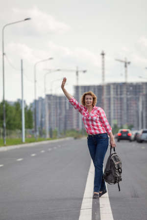 Hitchhiker waving hands for car stop, attractive mature woman with backpack standing on roadside line