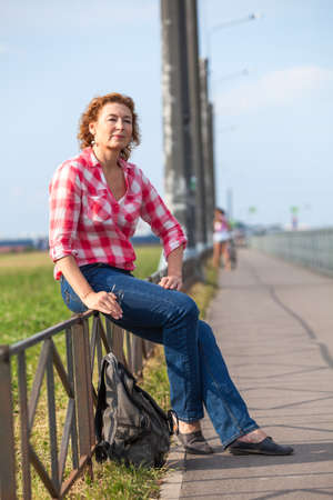 Mature Caucasian woman hitchhiker sitting near road and waiting the car for ride