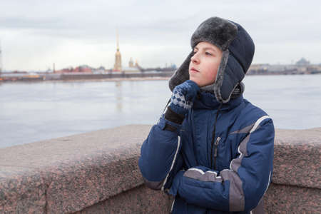 Teenage boy dressed warm jacket and hat with earflaps thinking, Peter and Paul fortress is on a background, granite bridge in St. Petersburg, Russia Stock Photo