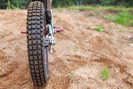 Rutschfeste Lauffläche auf Motorradreifen, Motocross-Fahrrad auf Sandpiste, Rückansicht, Exemplar