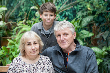 Portrait of grandpa and grandma with their grandson, Caucasian people family, looking at camera