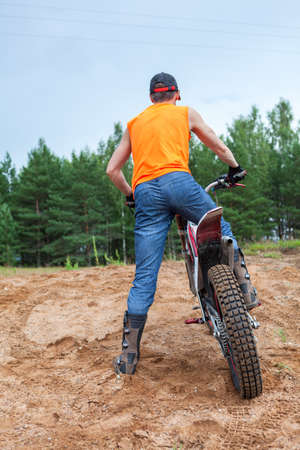Riding motorcross motorcycle in sandy pit, Caucasian man dressed orange t-shirt standing with a bike, rear view