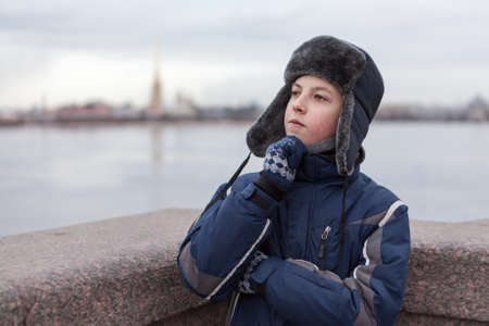 Teenager dressed warm jacket and hat with earflaps thinking, Peter and Paul fortress is on background, granite bridge across Neva river in St. Petersburg, Russia