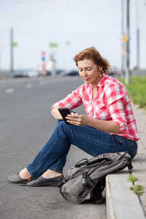 Mature Caucasian woman using smartphone for call for a taxi, sitting on a roadside with backpack
