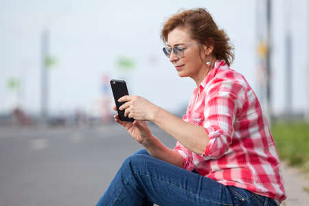 Mature woman dial-a-taxi using smartphone app, sitting on an urban road