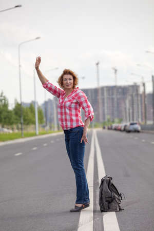 Middle age woman hail a taxi on road, stands on a lane with backpack on asphalt