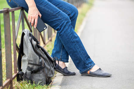 Cropped image of traveler person sitting on steel road fence, backpack is on ground, legs and hand holding cellular