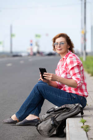 Smiling mature woman sitting on sloping curb, smartphone in her hands, looking far away, empty urban road