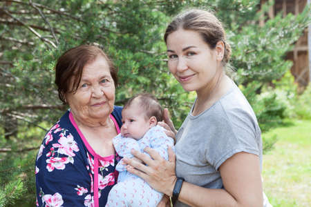 Great grandmother with her granddaughter and great-granddaughter, three people portrait at summer season