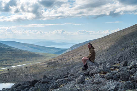 Contemplative man hiker sitting on stones of mountain peak at early morning, seen pleasant outlook over mountains