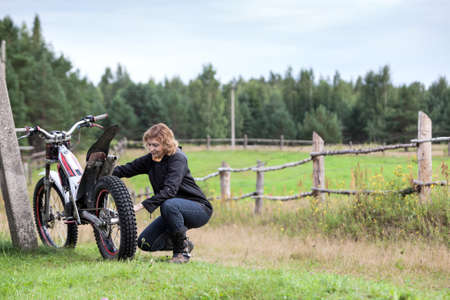 Middle age woman trying to repair her motorcycle, countryside road in farmland, copyspace
