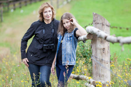 Portrait of mature mother and young daughter standing together near farm paddock, looking at camera, autumn season Reklamní fotografie