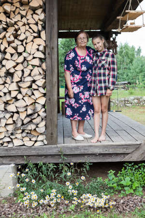 Grandmother and granddaughter standing on the veranda of summer house, next to the woodpile, full-length portrait