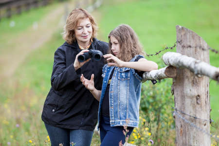 Mother gives binoculars young daughter and explains how to use it, woman and girl in a farmland
