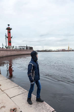 Teenage boy is on granite embankment of Neva river, near Rostral Column with view at the Peter and Paul Fortress from water, winter season in Saint-Petersburg, Russia