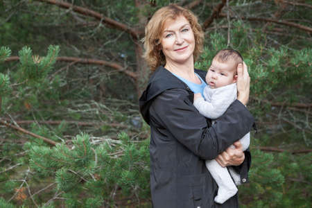 Middle age Caucasian woman standing with infant on arms, portrait against evergreen tree
