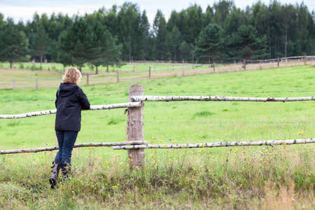 Woman enjoying rural view, standing her back to camera, keeping hands on wooden fence, farmland Banco de Imagens - 131033629