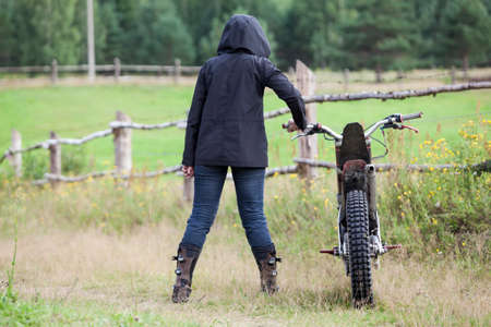 Rear view at female dressed black raincoat with hood on head standing with dirt motorcycle on countryside road in village