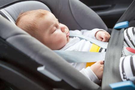 Sleeping Caucasian baby buckled into rear-facing car seat, close up view 版權商用圖片