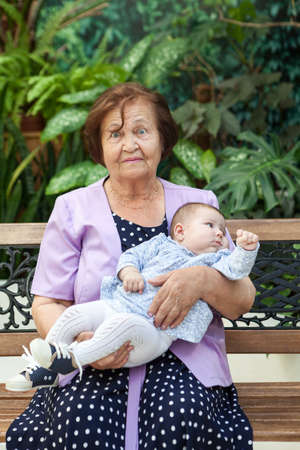 Senior Caucasian grandmother holding baby in arms, sitting on bench in green garden