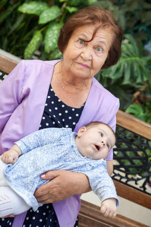 Senior grandmother sitting on becnh with grandchild laying on arms, elder Caucasian woman with infant portrait 写真素材