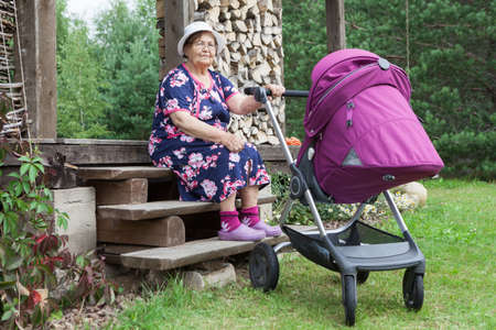 Portrait of happy smiling grandmother sitting on porch on summer sunny day with pram with newborn baby, courtyard