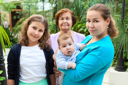 Caucasian family portrait with adult mother with newborn son and his teen age sister, grandmother stands behind them