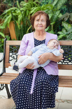 Loving grandmother sitting with her newborn baby grandson in bench next to a big green garden