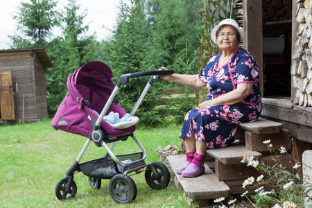 A woman of retirement age walks with a children pram in the yard of a summer cottage, near the wooden house, courtyard 写真素材