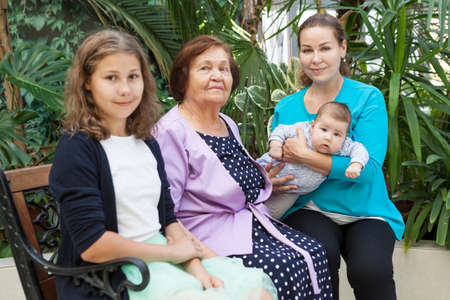 Young Caucasian mother holds a infant in her arms, sitting next to her preteen daughter and grandmother on bench in greenhouse