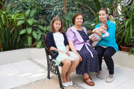 Womankind from infant, preteen girl, adult woman and senior grandmother, family is in greenhouse on the bench