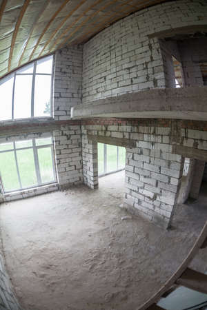 Second-level space with high windows from floor to ceiling, gas concrete block unfinished house, interior