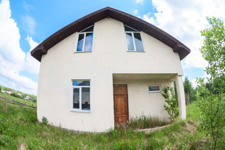 Front facade of country house with external finishing, real realty with plot of land for sale, wide angle view Reklamní fotografie