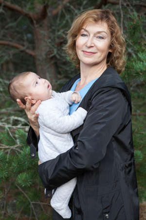 Middle age Caucasian woman with infant on arms, portrait outdoors Stock Photo