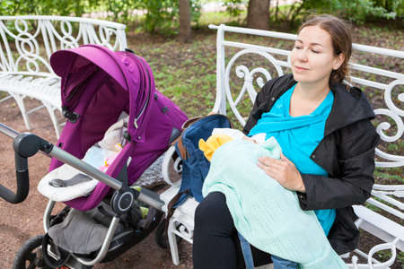 Young Caucasian mother nursing a baby in park on a bench. Breastfeeding in public place covering with blanket