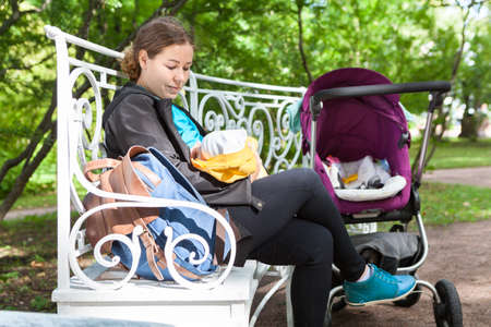 Woman is breastfeeding her child in a park, sitting on a bench, hiding behind a stroller