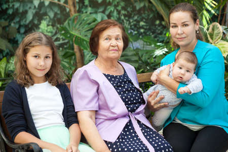 Portrait of three generations of women being close, great-grandmother, mother with teenage daughter and baby on arms Stock Photo