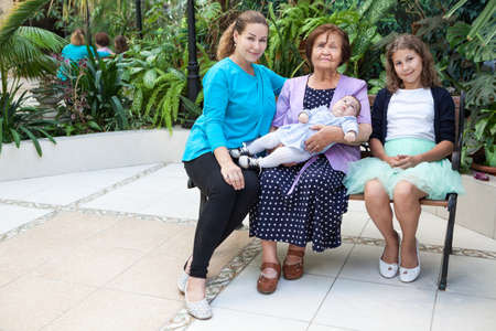 Great-grandmother with adult granddaughter and great-granddaughters sitting on bench, family portrait