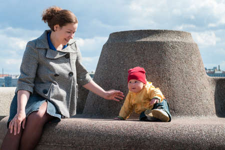 Stylish mother and child sitting near the parapet on embankment of the river, woman with boy toddler Stock Photo