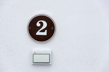 House number with a door bell on white wall, close-up view, copyspace