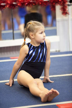 Young Caucasian gymnast sitting on gymnastic platform, four years old girl engages in sport school Stock Photo - 135481225