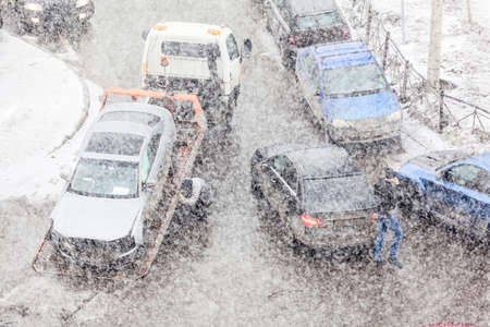 Tow truck lifting broken car from crossroad after road crash. Heavy snowfall at winter. Unrecognizable persons, blurred Stock Photo