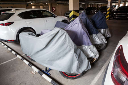 Motorcycles are parked on underground parking lot, covered with tents, standing between white cars